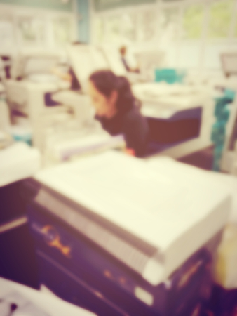 blurred image of worker is working at modern office copy documents on machine for copy, document printing and pagemaking for a book. vintage tone