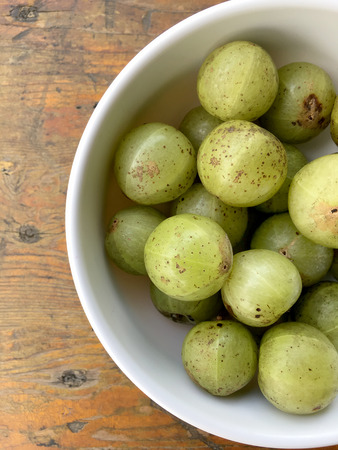 Delicious indian gooseberry in a small white blow on wooden table, local fruits and herbs with medicinal properties much of Thailand. Stock Photo