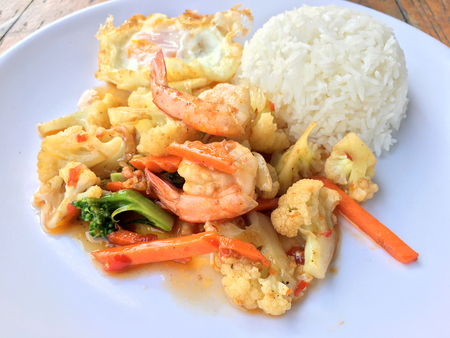 stir-fry vegetables with bean curd and shrimp in white dish with rice and fried egg on wooden background. Thai style Food. 스톡 콘텐츠