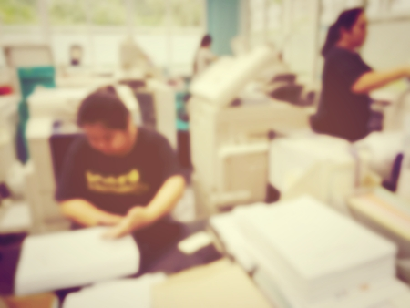 blurred image of worker is pagemaking for a book at modern office. vintage tone