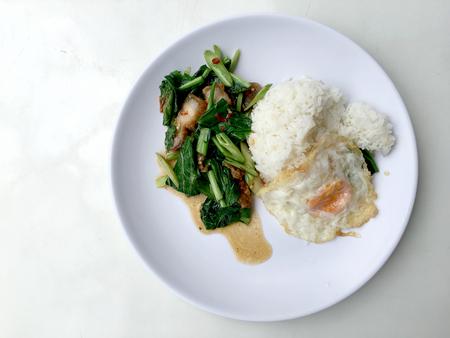 Stir fry Kai Land and crispy pork, stir fried rice with rice in white dish on white background. Thai style food. Stock Photo