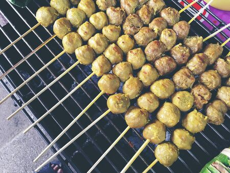 Thai meatballs on a grill on the steel stove on fire at the market. Thai street food. vintage tone.