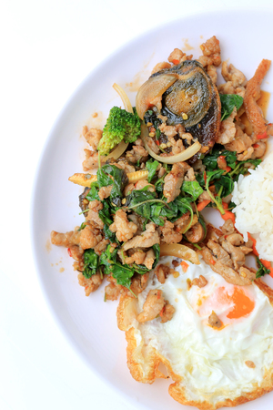 Stir-fried basil leave with minced pork, chicken, fried preserved egg and carrot, yellow corn, Broccoli with rice and fried egg in white dish on white background. Thai style food.