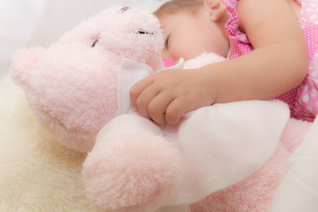 Baby drinking water or milk from a small bottle and lying on bed while hugging pink teddy bear in the bedroom because the baby having fever and attach cooling gel pad on her forehead for relief fever.
