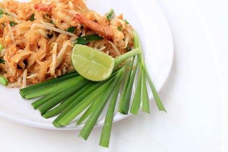 Pad Thai, stir-fried rice noodles with shrimp in white plate with slide lemon and green vegetable. The one of Thailands national main dish. the popular food in Thailand. Thai Fried Noodles