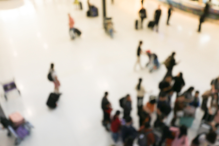 blurred image of crowd of travelling people or passenger walking with a luggage from flight in the international airport terminal with beautiful bokeh from the light,advertise & traveling concept.