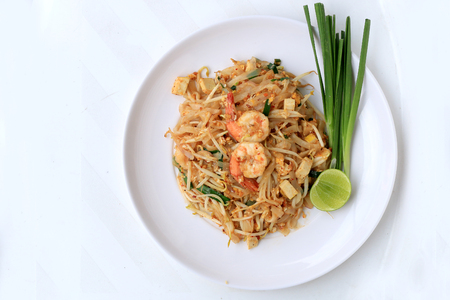 Thai style noodles, Pad Thai, stir-fried rice noodles with shrimp serve with vegetable in white plate on white background. The one of Thailand's national main dish. the popular food in Thailand. 免版税图像