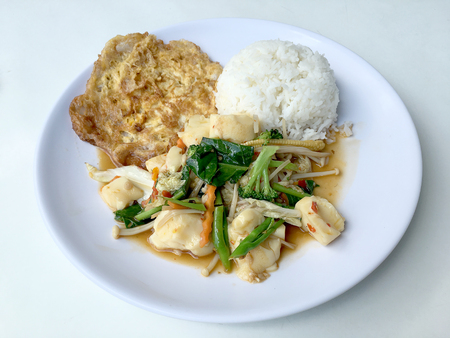Stir vegetables with Tofu in chinese style with gravy Sauce and thai style omelet with rice in white plate on background. Vegetarian Food, healthy food.