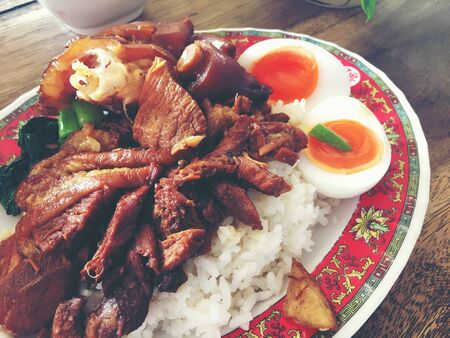 Rice with pork legs with boiled egg and sweet gravy sauce style chinese food in dish on the table, Thai food.Famous food in Thailand