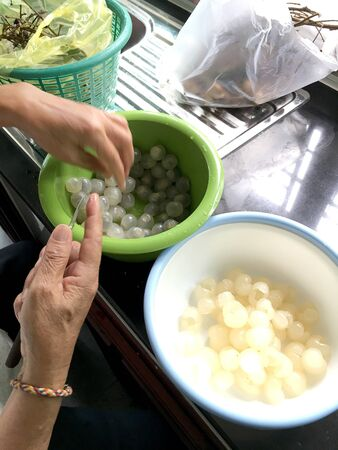 Hand of woman is fresh peel longan fruit or dimocarpus longan from small knife for remove skin from longan bark in a blow at the kitchen. Thai and Exotic fruit. Cooking Concept