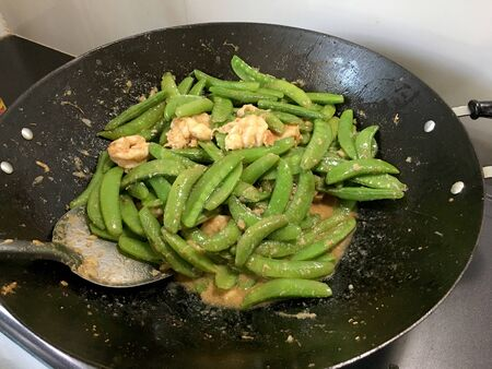 Vegetables Stir-Fry Recipe of pea with prawns or shrimps in black iron pan at the kitchen. Cooking concept. Standard-Bild