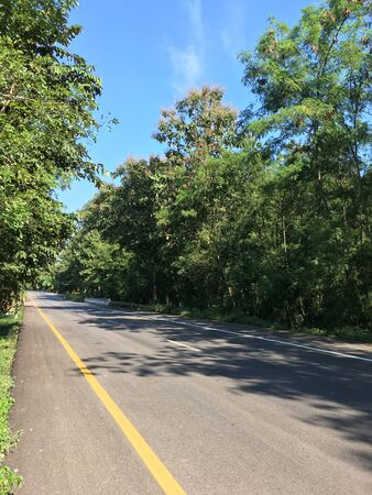 Beautiful local asphalt road way to the natural in rainy season with trees forest, blue sky and mountains in the backgrounds in the north of Thailand. Standard-Bild