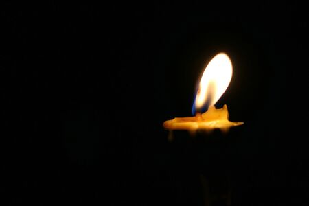 One or Single yellow light candle burning brightly in the black background, candle light isolated black in dark night.