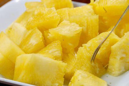 Cerrar la textura de fondo de rodaja de piña en un plato blanco. Tobogán y trozo de fruta fresca.