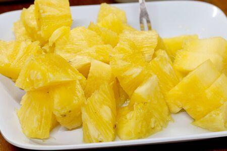 Close up slice pineapple background texture in white dish. Slide and piece of fresh fruit.