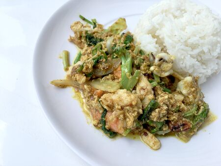 Stir fry mixed-seafood with with yellow curry powderin thai style with fried egg and rice in in white plate on white background. Standard-Bild - 136054184