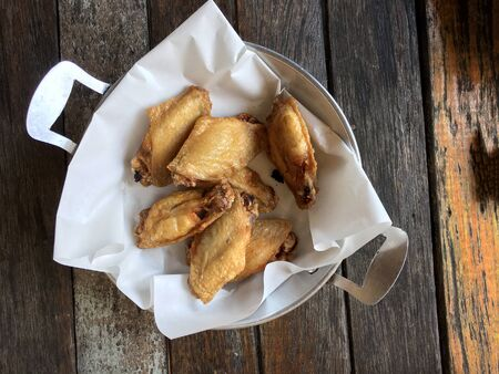 Deep fried chicken wing with garlic sauce in bucket. on wooden table for asian food concept. Thai style food. Standard-Bild - 136054235
