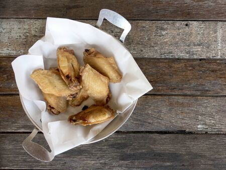 Deep fried chicken wing with garlic sauce in bucket. on wooden table for asian food concept. Thai style food.