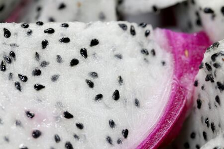 Healthy dragon fruit or pitaya pieces background, close up of beautiful fresh sliced dragon fruit with texture in the market in thailand. Pitaya is the plant in Cactaceae family or Cactus.