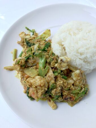 Stir fry mixed-seafood with with yellow curry powderin thai style with fried egg and rice in in white plate on white background.