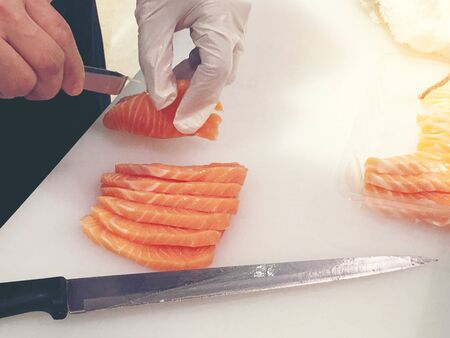 Sliced raw salmon or fresh salmon. Salmon fillets for sale at market displayed with a patchwork effect. Many fresh salmon fish meat slices in a black tray which are sale in the supermarket. Standard-Bild