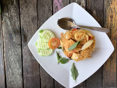 Fried rice with shrimp and vegetable in white plate on the on beautiful wooden table background from top view. Thai style food.