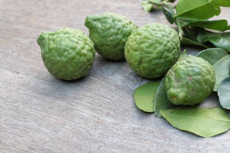 Group of fresh Bergamot fruit and bergamot leaves on wooden table background Standard-Bild - 151896944