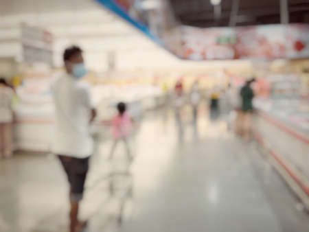 Blurred image of people shopping in supermarket. Cashier with long line of people waiting at checkout counter in fitness store at outlet shopping mall in Thailand. Standard-Bild - 158042314