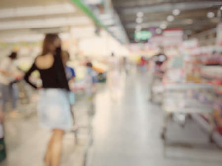 Blurred image of people shopping in supermarket. Cashier with long line of people waiting at checkout counter in fitness store at outlet shopping mall in Thailand. Standard-Bild