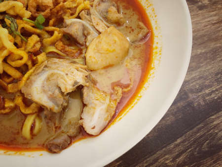 Khao Soi Kai, Thai spicy food in white blow on wooden table, Thai spicy soup. Thai Food. Northern Thai Style Curried Noodle Soup with Chicken Standard-Bild
