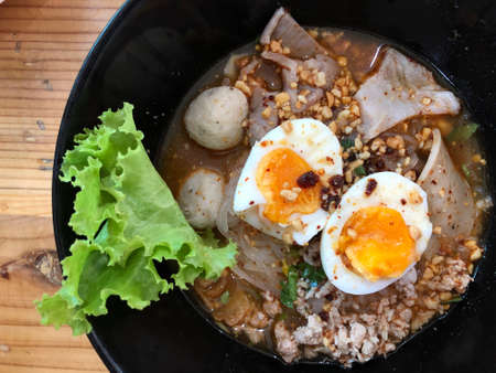 Spicy tom yam noodle soup with boiled egg, pork and big