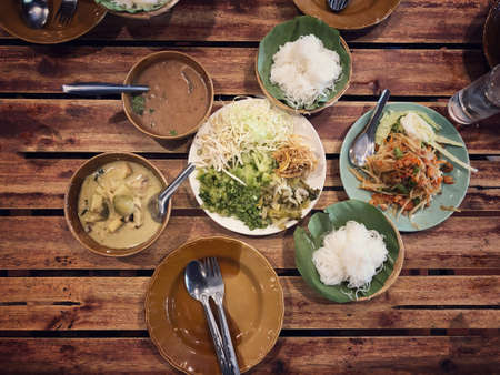 Rice noodles with curry sauce,  Green curry and fresh organic vegetable set on the table (eggplant, yardlong bean, banana blossom, pickled lettuce, bean sprouts, hairy basil) . Thai style food. Standard-Bild - 158042110