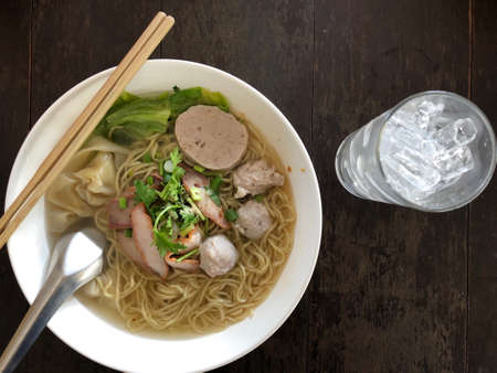 Thai noodle soup wonton roasted pork / yellow egg noodle with pork dumpling and chinese cabbage vegetable in soup bowl on wooden table top view. Thai style food.