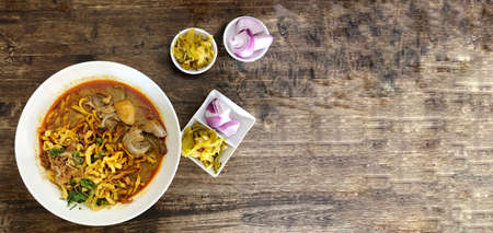 Khao Soi Kai, Thai spicy food in white blow on wooden table, Thai spicy soup. Thai Food. Northern Thai Style Curried Noodle Soup with Chicken Standard-Bild - 158042166