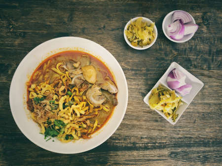Khao Soi Kai, Thai spicy food in white blow on wooden table, Thai spicy soup. Thai Food. Northern Thai Style Curried Noodle Soup with Chicken Standard-Bild - 158042339