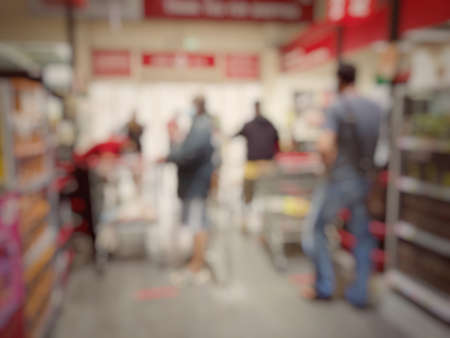 Blurred image of people shopping in supermarket. Cashier with long line of people waiting at checkout counter in fitness store at outlet shopping mall in Thailand. Standard-Bild - 158042225