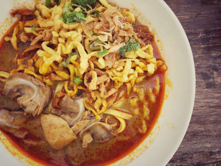 Khao Soi Kai, Thai spicy food in white blow on wooden table, Thai spicy soup. Thai Food. Northern Thai Style Curried Noodle Soup with Chicken Standard-Bild - 158128101