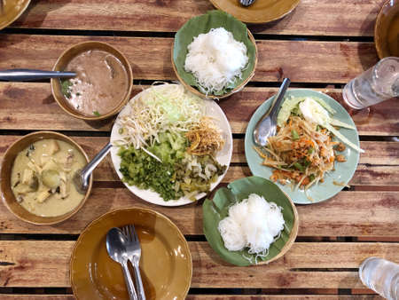 Rice noodles with curry sauce,  Green curry and fresh organic vegetable set on the table (eggplant, yardlong bean, banana blossom, pickled lettuce, bean sprouts, hairy basil) . Thai style food. Standard-Bild - 158042266
