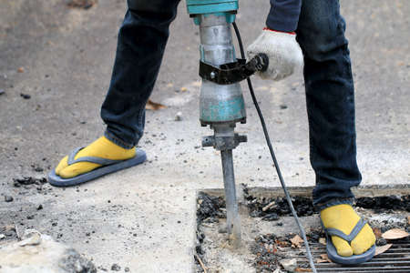 Male workers use electric concrete breaker for digging and drilling concrete repairing driveway surface with jackhammer at the local city road, during sidewalk, work construction site.