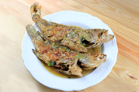 Thai Giant gourami fish and garlics deep fried and sweet spicy sauce in white dish on pine wooden table. Deep fried fish with Sweet chili. Thai food fried fish with spicy sauce. Thai style food.