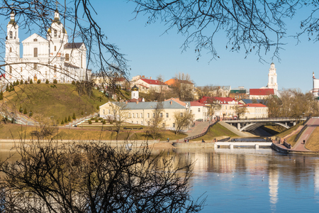 City architecture, on the bank of the river there is a Christian church, a monastery of the princess, a chapel  town hall, a small bridge connects, two banks, footpaths, a sunny day, Belarus Vitebsk