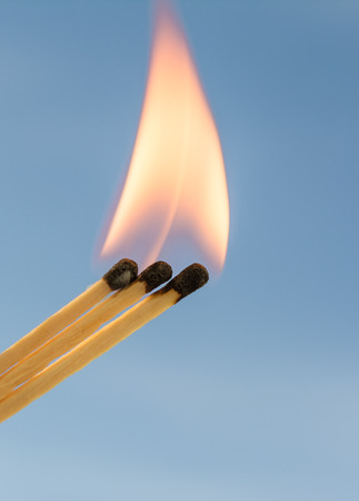 Three burning matches on a blue sky background