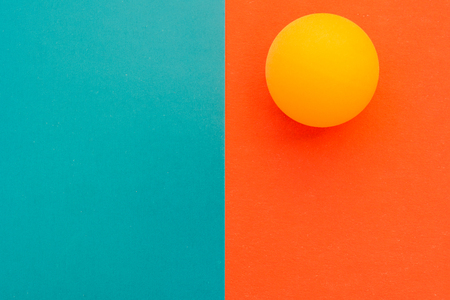 One yellow tennis ball on a red blue background