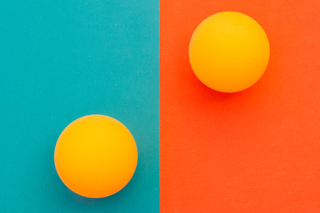 two yellow tennis balls on a red blue background