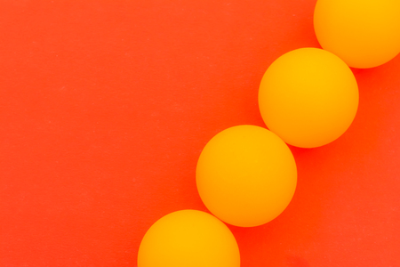 A sequence of four yellow tennis balls on a red background