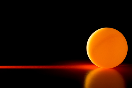 Yellow ball on a red dark background illuminated by a side beam of light, abstract background