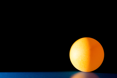 Yellow ball on a blue dark background illuminated by a side beam of light, abstract background