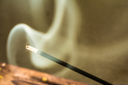 Burning incense sticks and smoke on dark background Banco de Imagens