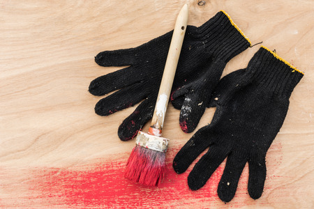 home decorating: Black gloves stained in paint and paintbrush in red paint lie on plywood, abstract composition Stock Photo
