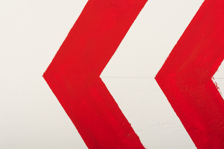 Red arrow indicates direction to the left painted with paint on a white wall, abstract background